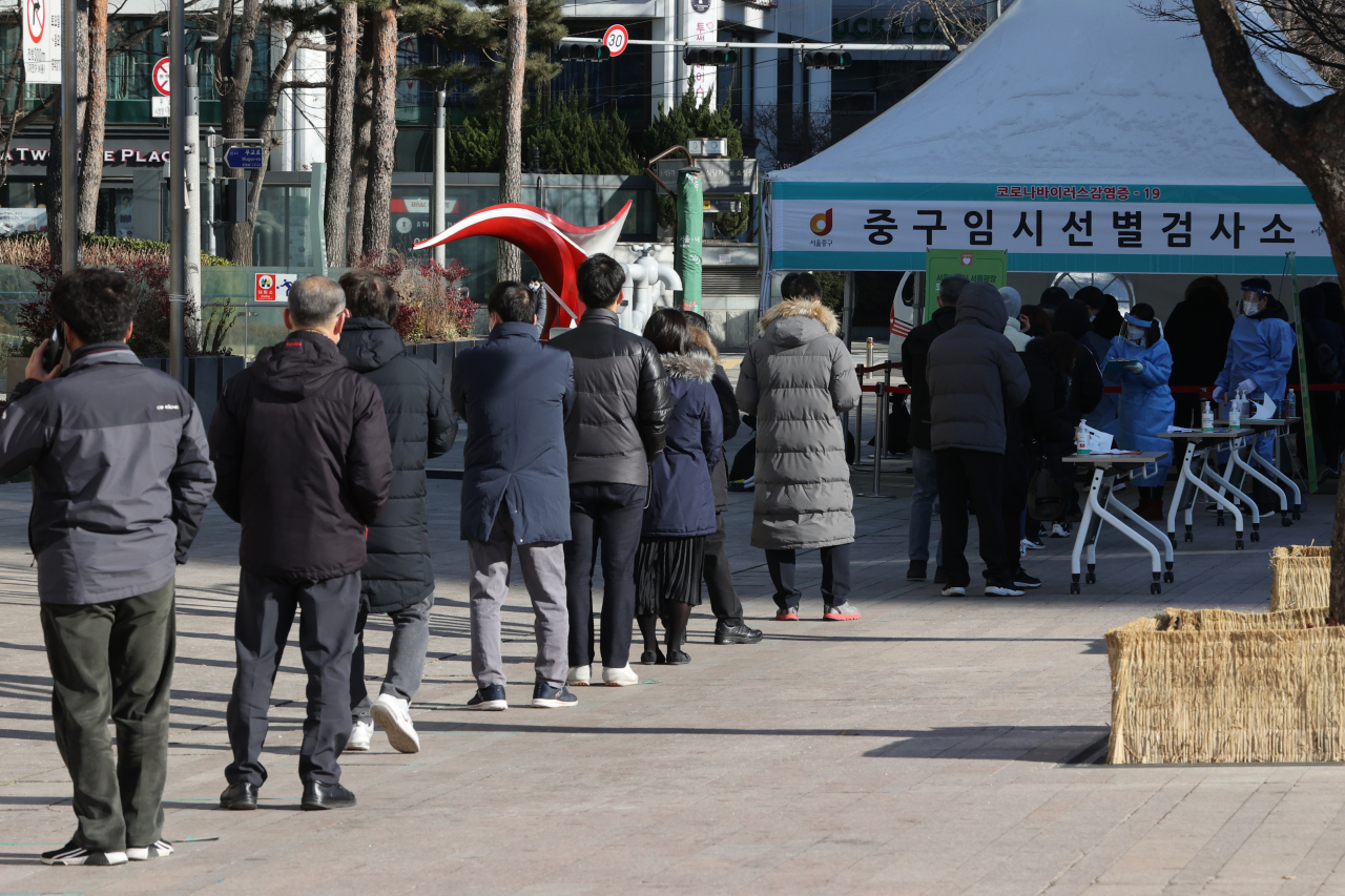 People stand in line to take coronavirus tests at a temporary screening center in front of Seoul City Hall in downtown Seoul on Sunday. (Yonhap)