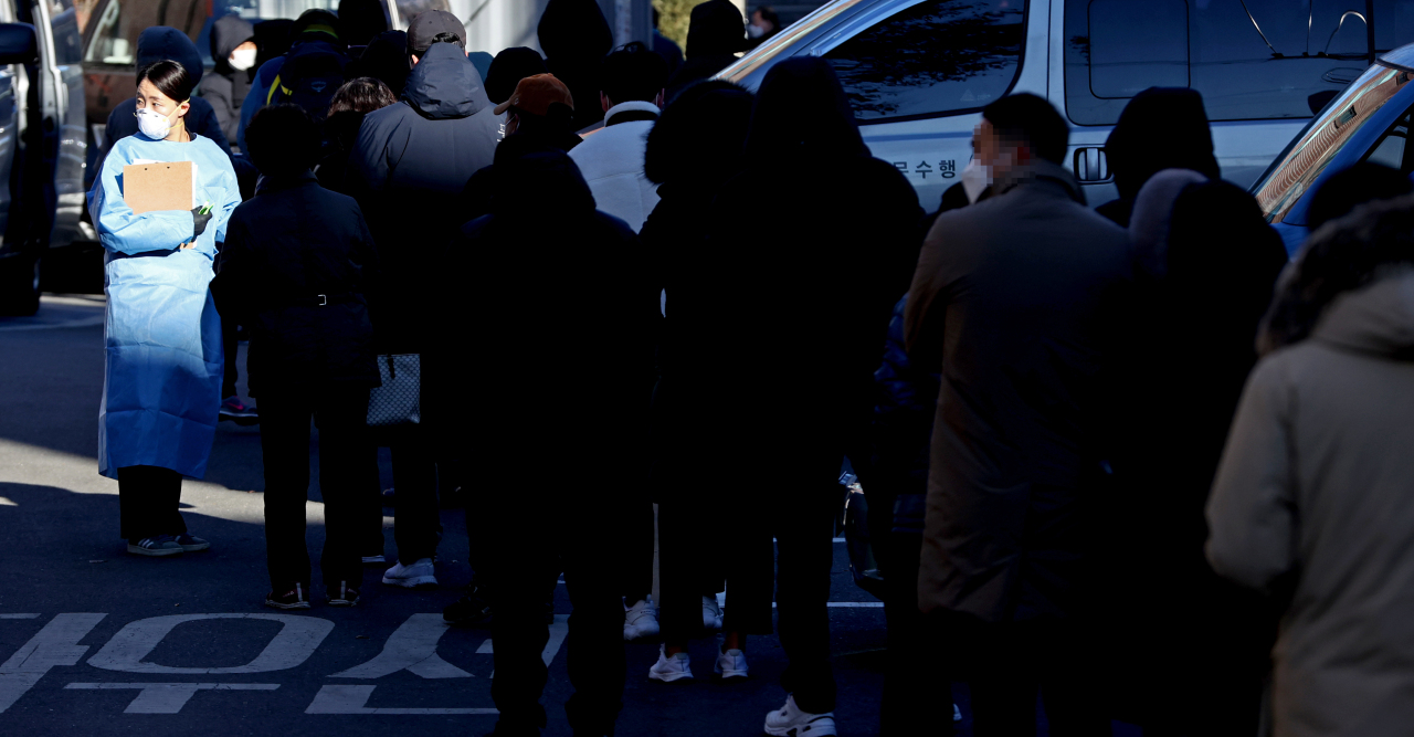 People wait in a long line Saturday for diagnostic checks at a COVID-19 center in Jongno-gu, central Seoul. The government is faced with potential shortage of medical workers with the number of new daily cases sharply rising under the third coronavirus wave. (Yonhap)