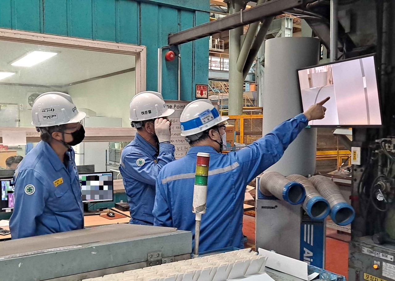 Posco employees examine a product identified by the company's product recognition program. (Posco)