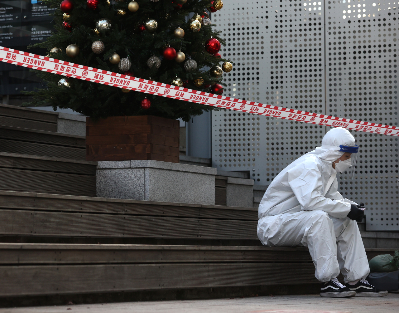 A health care worker wearing personal protective equipment takes a break at a testing center in Seoul on Christmas Eve. (Yonhap)