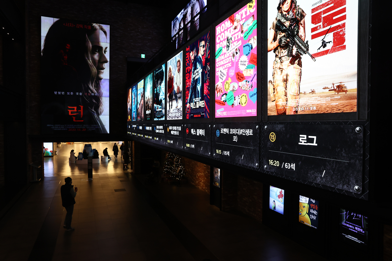 A man walks past movie posters at a cinema in Seoul on Dec. 7. (Yonhap)