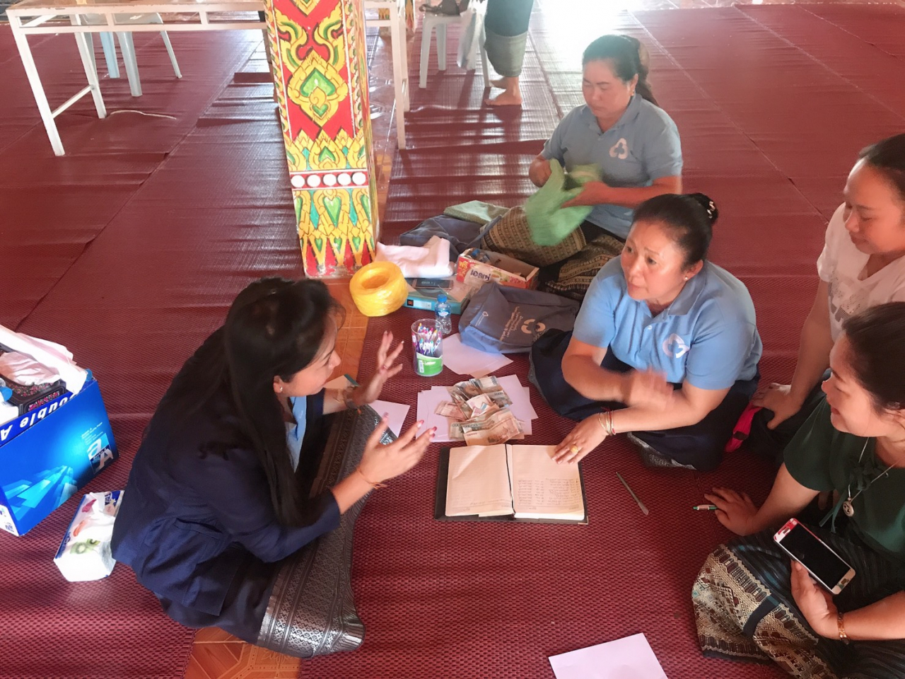 An official from the Lao government teaches members of Saemaul Geumgo in Phonhong district, Vientiane Province on how to write account books. (Korean Federation of Community Credit Cooperatives)