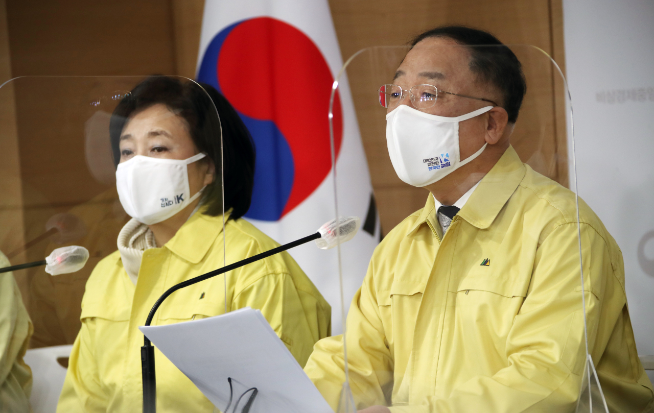 Finance Minister Hong Nam-ki (right) speaks during a press conference to announce a fresh economic relief package in response to a third wave of COVID-19 infections, at the government complex in Seoul, Tuesday. (Yonhap)