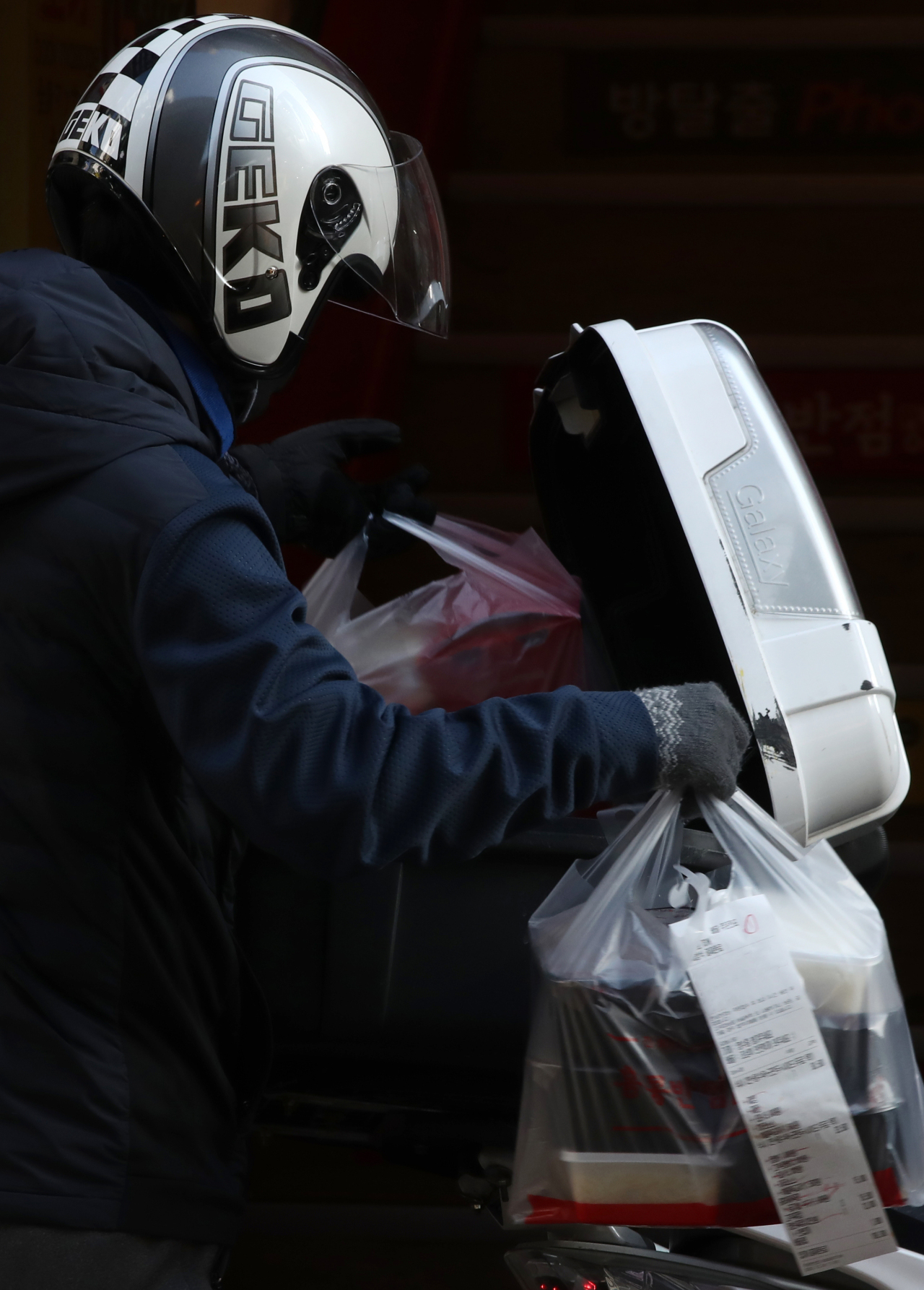 A delivery service worker carries packaged meals in Myeong-dong, one of the busiest shopping districts in Seoul, on Thursday, amid a surge in coronavirus cases. South Korea has imposed a nationwide ban on gatherings of five or more people as part of efforts to stem the spread of the coronavirus. (Yonhap)