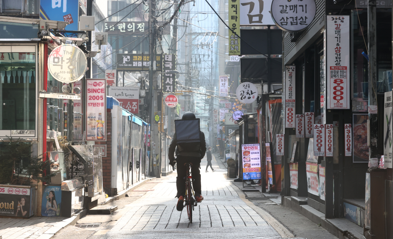 A man riding a bicycle for food delivery passes through restaurants near Gangnam Station, Seoul, Dec. 24. (Yonhap)