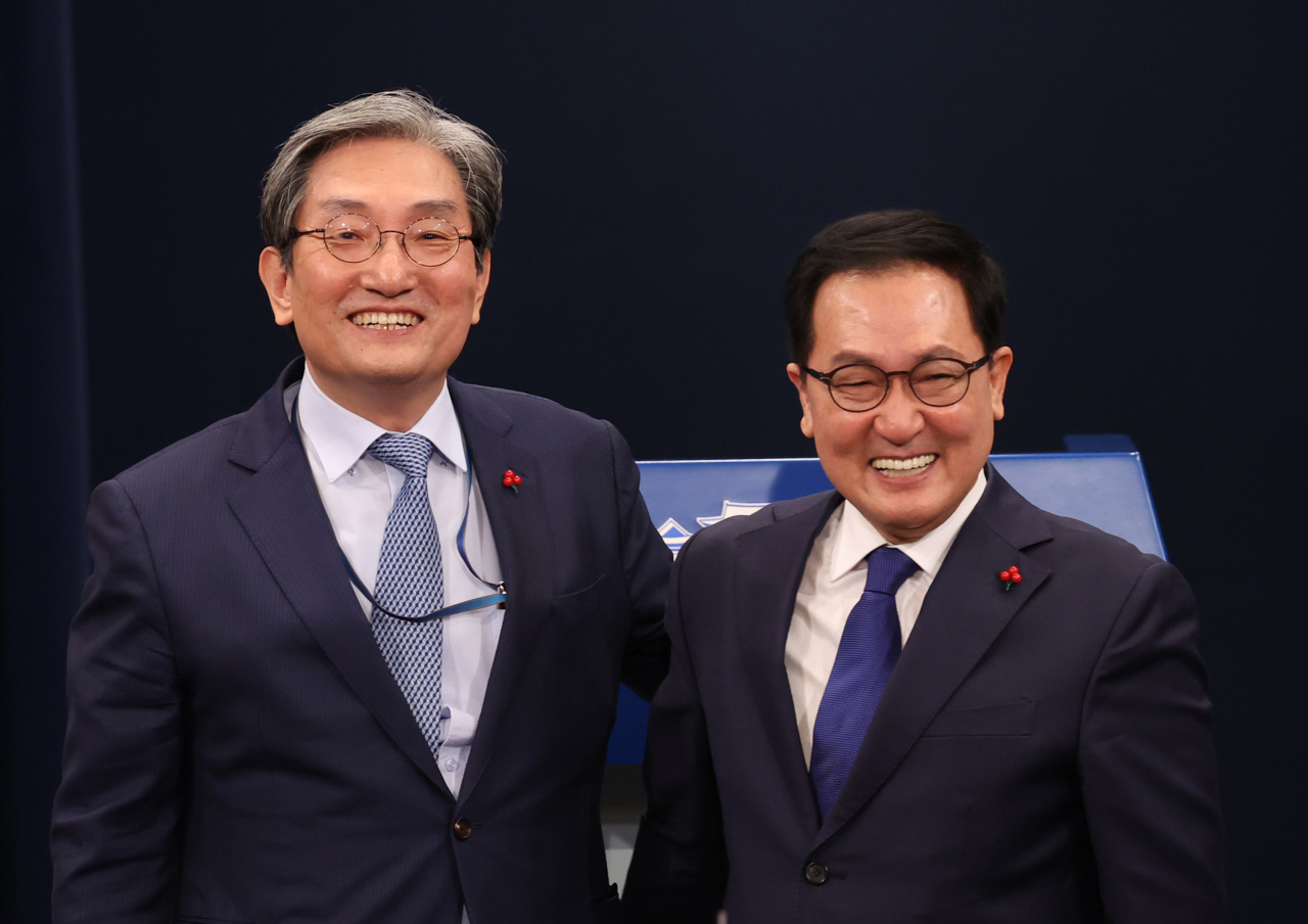 You Young-min (right), newly appointed presidential chief of staff, and his predecessor Noh Young-min, pose at a press briefing at Cheong Wa Dae on Thursday. (Yonhap)