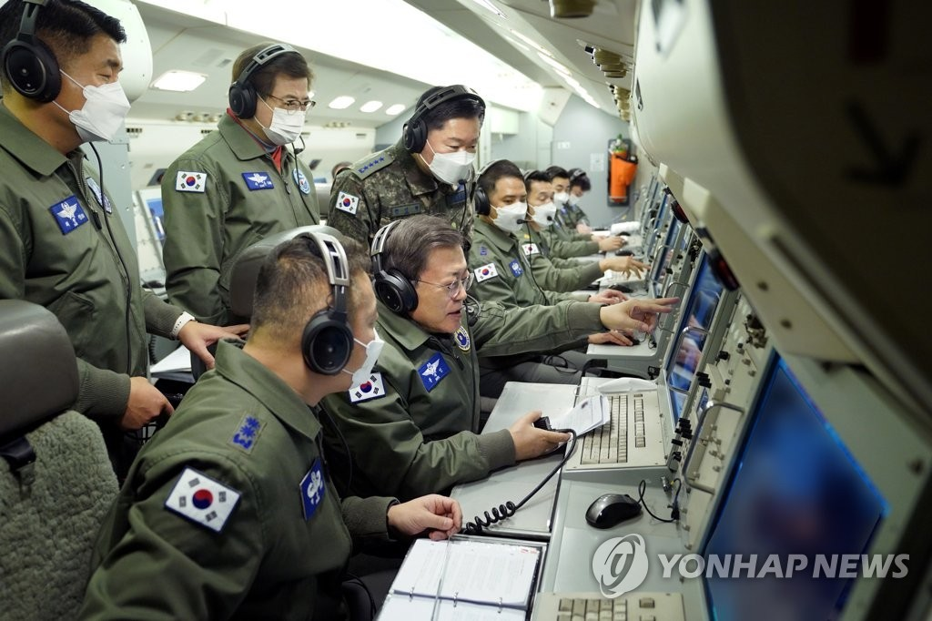 President Moon Jae-in (C) inspects South Korea's combat readiness aboard a Peace Eye aircraft during its two-hour patrol mission on Jan. 1, 2021, in this photo provided by his office. (Yonhap)