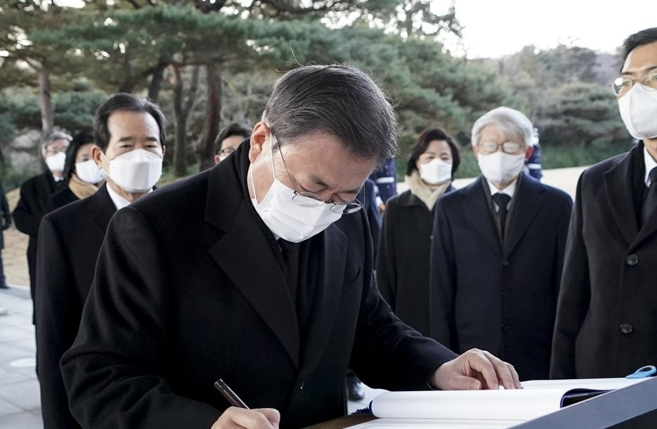 President Moon Jae-in writes a message in the visitors' book at Seoul National Cemetery in the southern part of the capital on Jan. 2, 2021. (Yonhap)