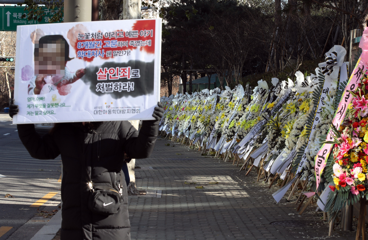 A protester demands murder charges for the adoptive parents whose abuse led to the death of a 16-month-old girl, in front of the Seoul Southern District Prosecutors Office on Dec. 14. (Yonhap)