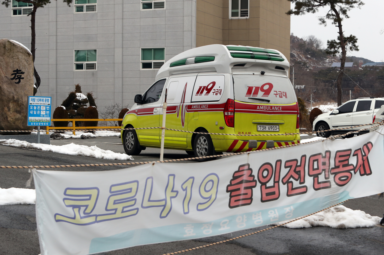 An ambulance is on standby Sunday to transport COVID-19 patients from an elderly care facility in Gwangju to nearby treatment centers. More than 50 confirmed cases have been reported from the elderly care facility by Sunday afternoon. (Yonhap)