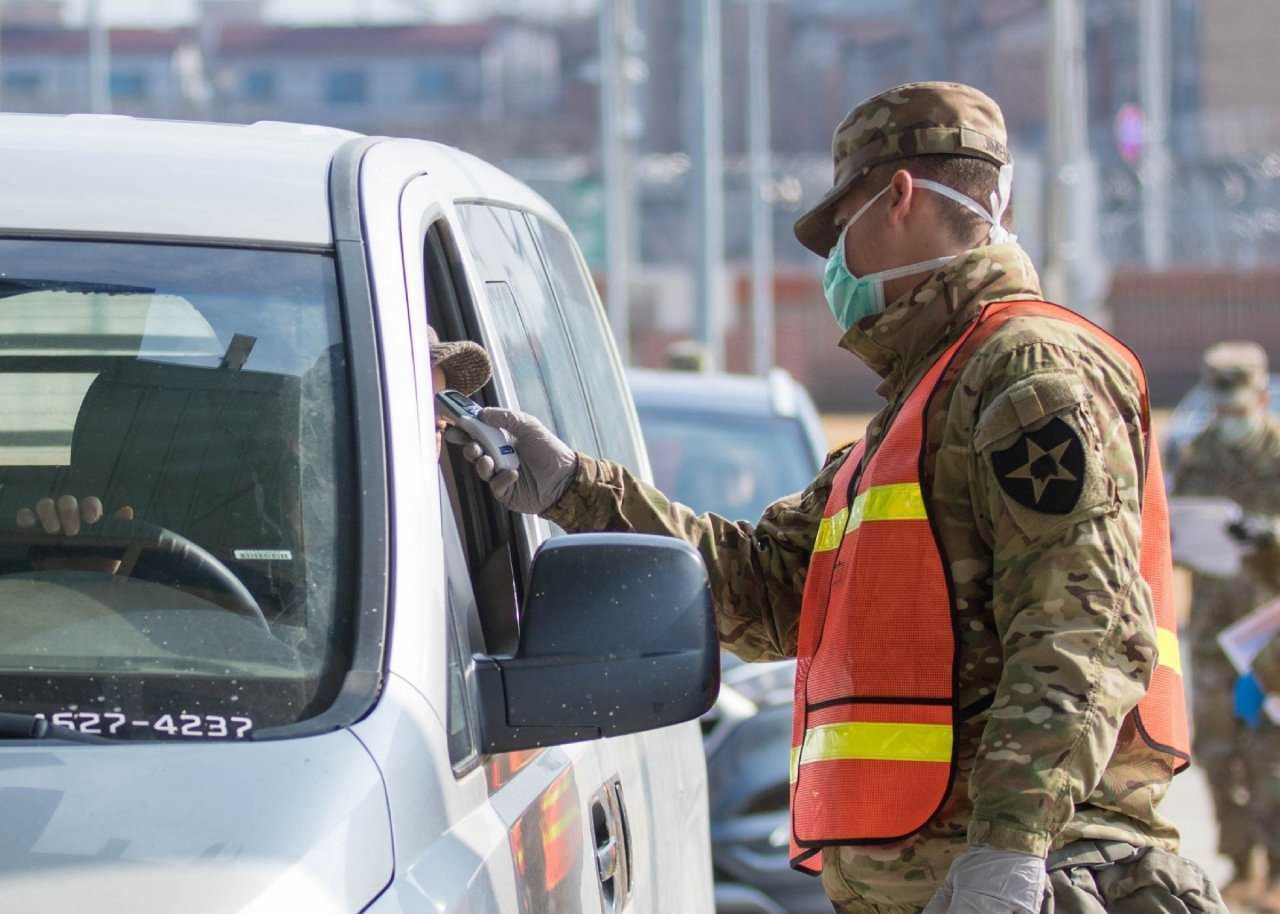 In this February file photo provided by the US Forces Korea, a military guard at US Army Garrison Humphreys in Pyeongtaek, 70 kilometers south of Seoul, checks the temperature of a driver to screen entrants to the compound for the novel coronavirus. (USFK)