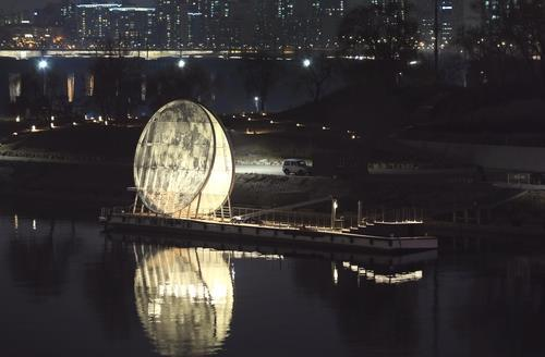 This photo, provided by the Seoul city government on Monday, shows a night view of the giant moon-shaped art installation by Nodeul Island in Seoul. (Seoul city government)