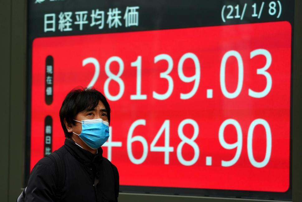 A man wearing a protective mask to help curb the spread of the coronavirus walks past an electronic stock board showing Japan's Nikkei 225 index at a securities firm Friday in Tokyo. (AP)