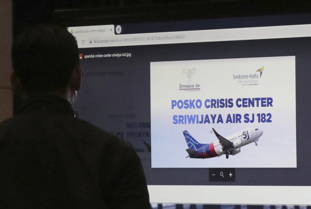 A man stands near an LCD screen installed at a crisis center set up following a report that a Sriwijaya Air passenger jet has lost contact with air traffic controllers after take off, at Soekarno-Hatta International Airport in Tangerang, Indonesia, Saturday. A Sriwijaya Air passenger jet with 56 passengers and six crew members onboard, lost contact with air traffic controllers after taking off from Indonesia's capital on Saturday on a domestic flight, officials said. (AP-Yonhap)