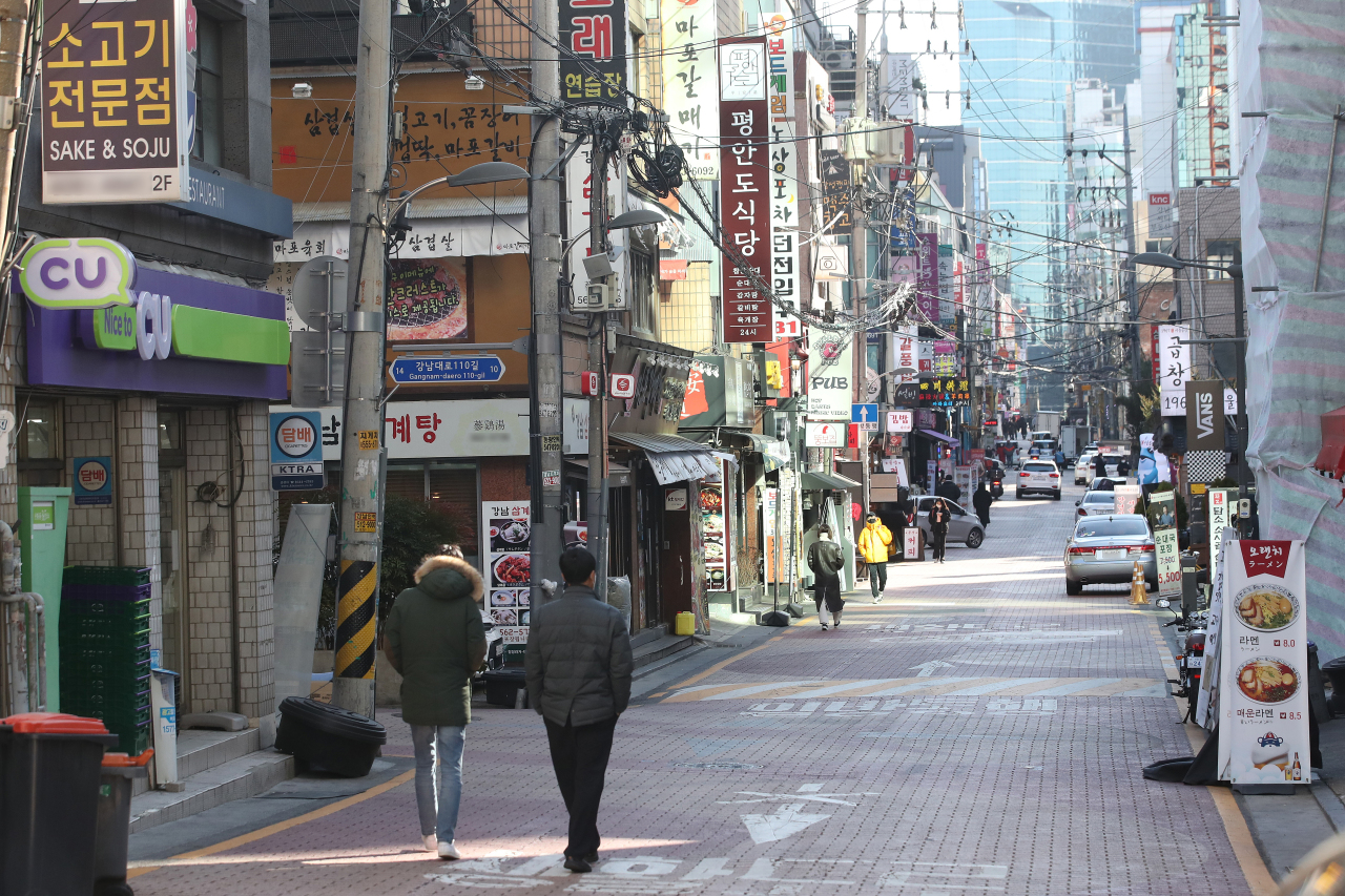Pedestrians walk through the quiet Gangnam district in Seoul on Dec. 14. (Yonhap)
