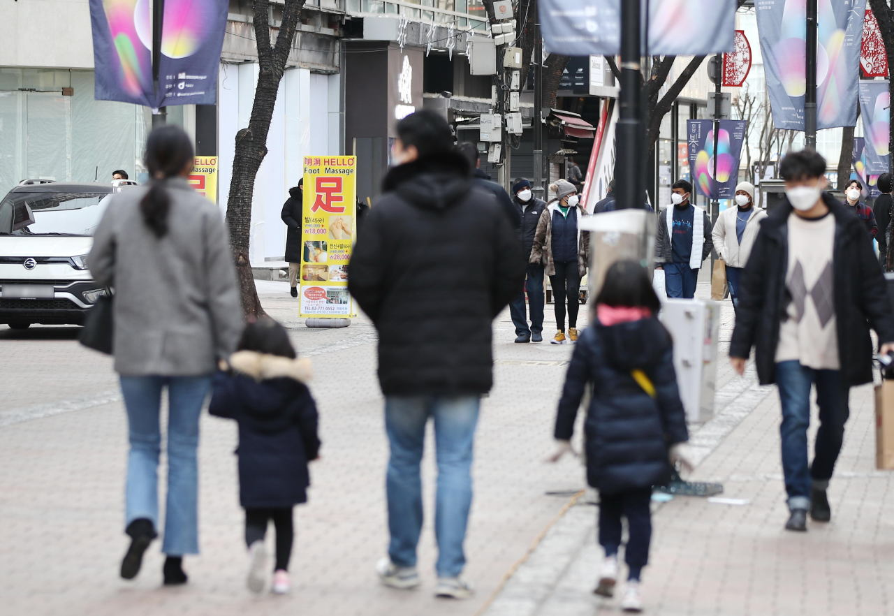 A family strolls through the Myeong-dong shopping district in central Seoul on Jan. 3. (Yonhap)