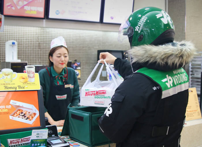 a Vroong delivery worker collects an order of donuts. (Mesh Korea)