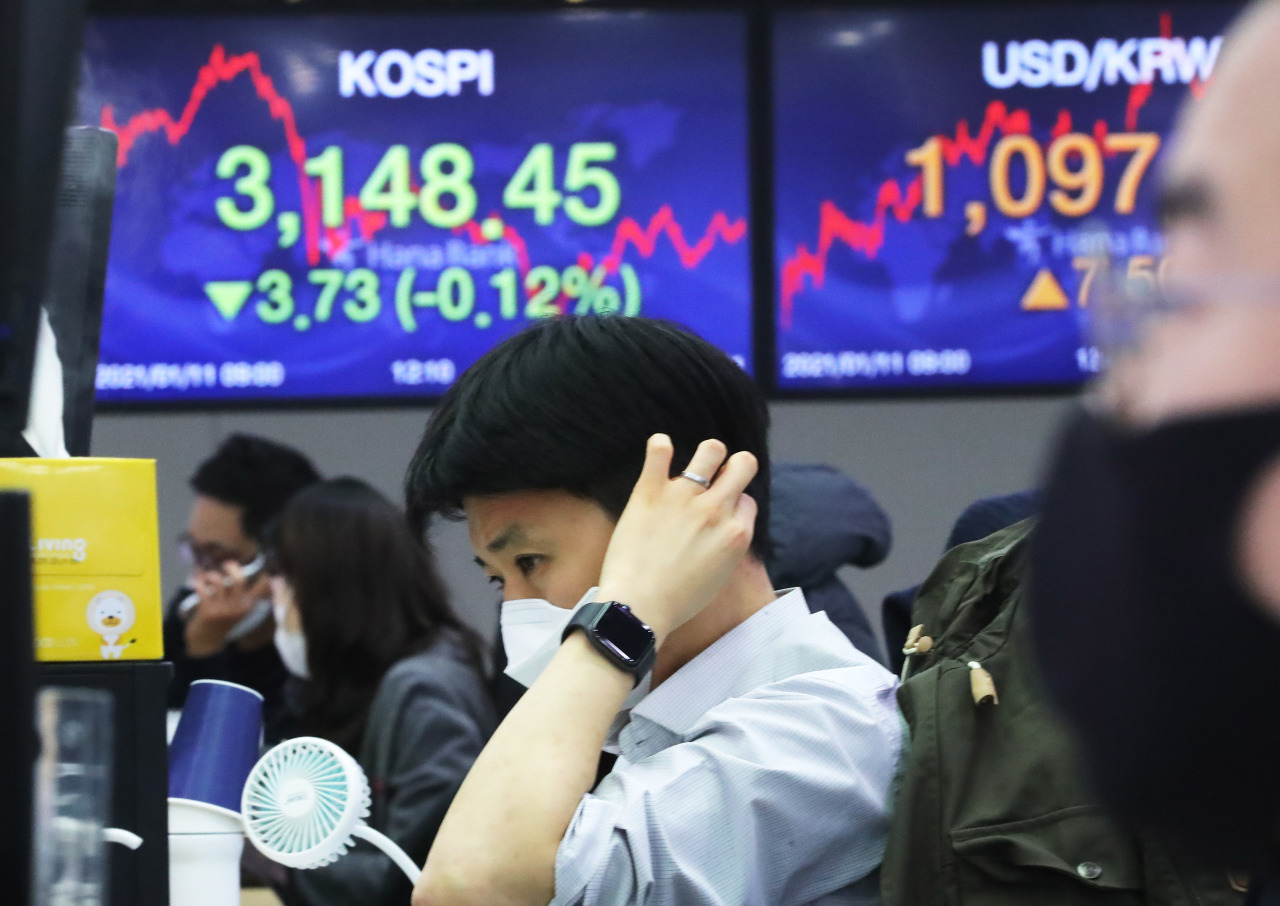 Electronic boards at Hana Bank's dealing room in Seoul show the benchmark Kospiclosed lower at 3,148.45 points Monday. (Yonhap)