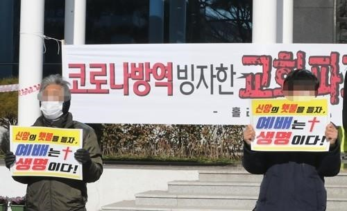 Two churchgoers holding signs calling for in-person worship services to be allowed at churches. (Yonhap)