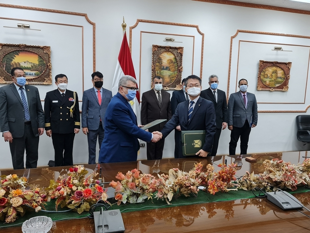 This photo, provided by Hanwha Techwin Co. on Tuesday, shows officials from Hanwha Techwin and Banha posing for a photo after signing a deal in Egypt. (Yonhap)