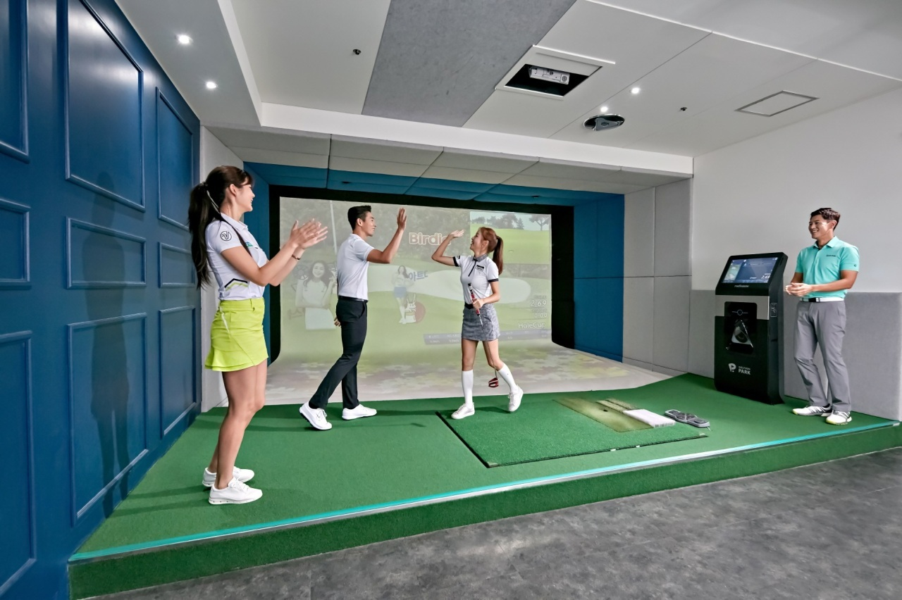 Users play the latest version of Golfzon's indoor golf simulator. (Golfzon)