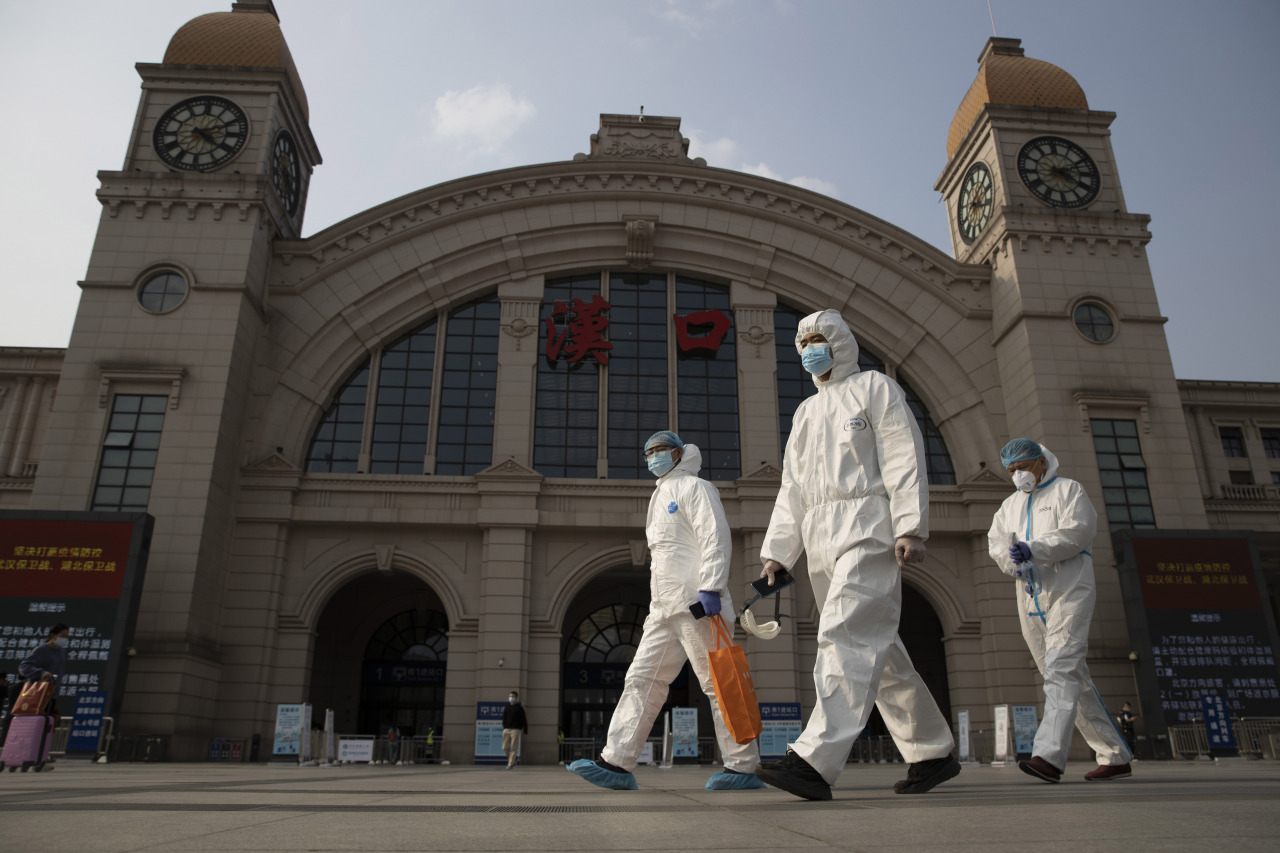 Workers in protective suits walk past the Hankou railway station in Wuhan in central China's Hubei province on April 7, 2020. (AP-Yonhap)