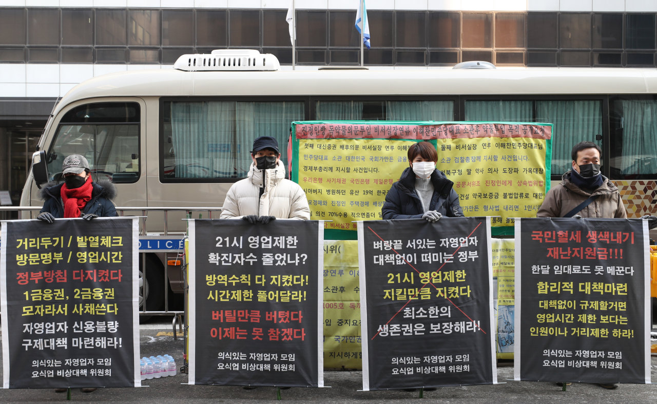 Members of a coalition for the rights of restaurant businesses stage a protest Tuesday near the headquarters of the ruling Democratic Party of Korea in Yeouido, western Seoul, to demand the government remove the 9 p.m. operations curfew under COVID-19 social distancing rules. (Yonhap)