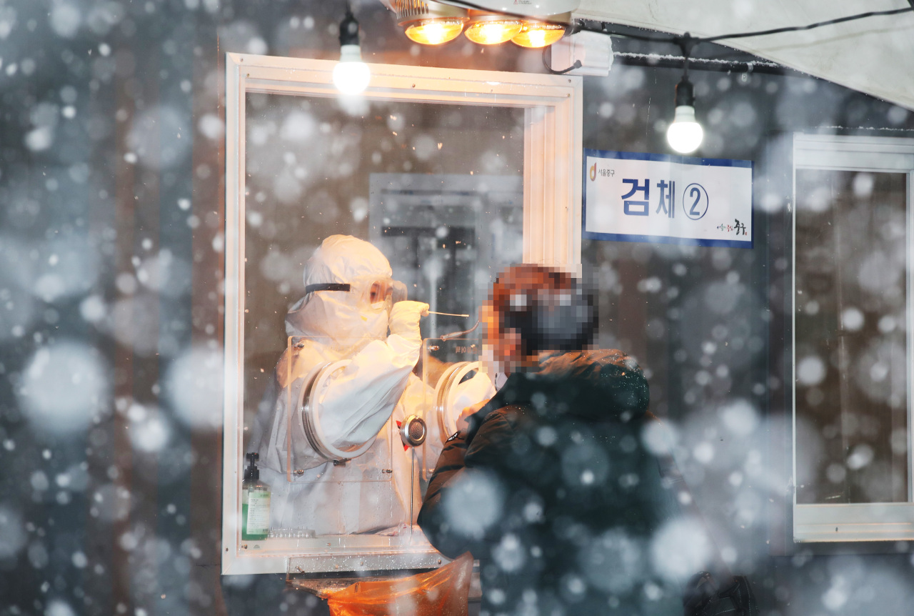 A medical worker collect specimens for coronavirus testing at a makeshift clinic in front of Seoul Station on Tuesday. (Yonhap)