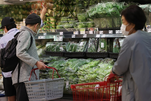 This file photo, taken Oct. 6, 2020, shows people looking at vegetables while grocery shopping at a discount store in Seoul. (Yonhap)