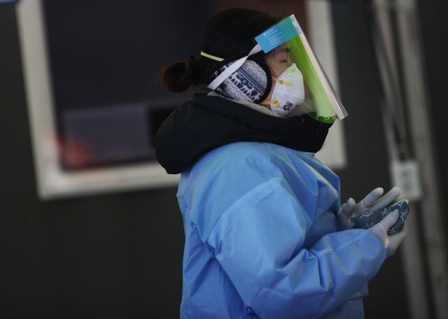 A medical worker warms her hands with instant hot packs at a makeshift clinic for coronavirus testing in front of Seoul Station on Sunday, amid a cold wave sweeping the country. (Yonhap)