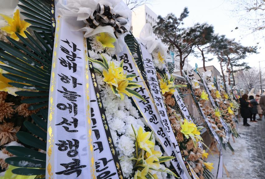 A row of funeral wreaths made of white and yellow flowers is laid alongside the wall of the Seoul Southern District Court on Wednesday. (Yonhap)
