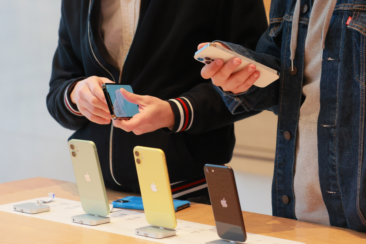 This file photo, taken Oct. 30, 2020, shows visitors at an Apple store in southern Seoul using iPhones. (Yonhap)