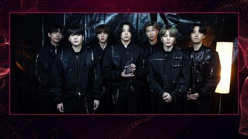 This photo, provided by Gaon Chart, shows BTS holding a trophy for the 2021 Gaon Chart Music Awards held on Wednesday. (Gaon Chart)