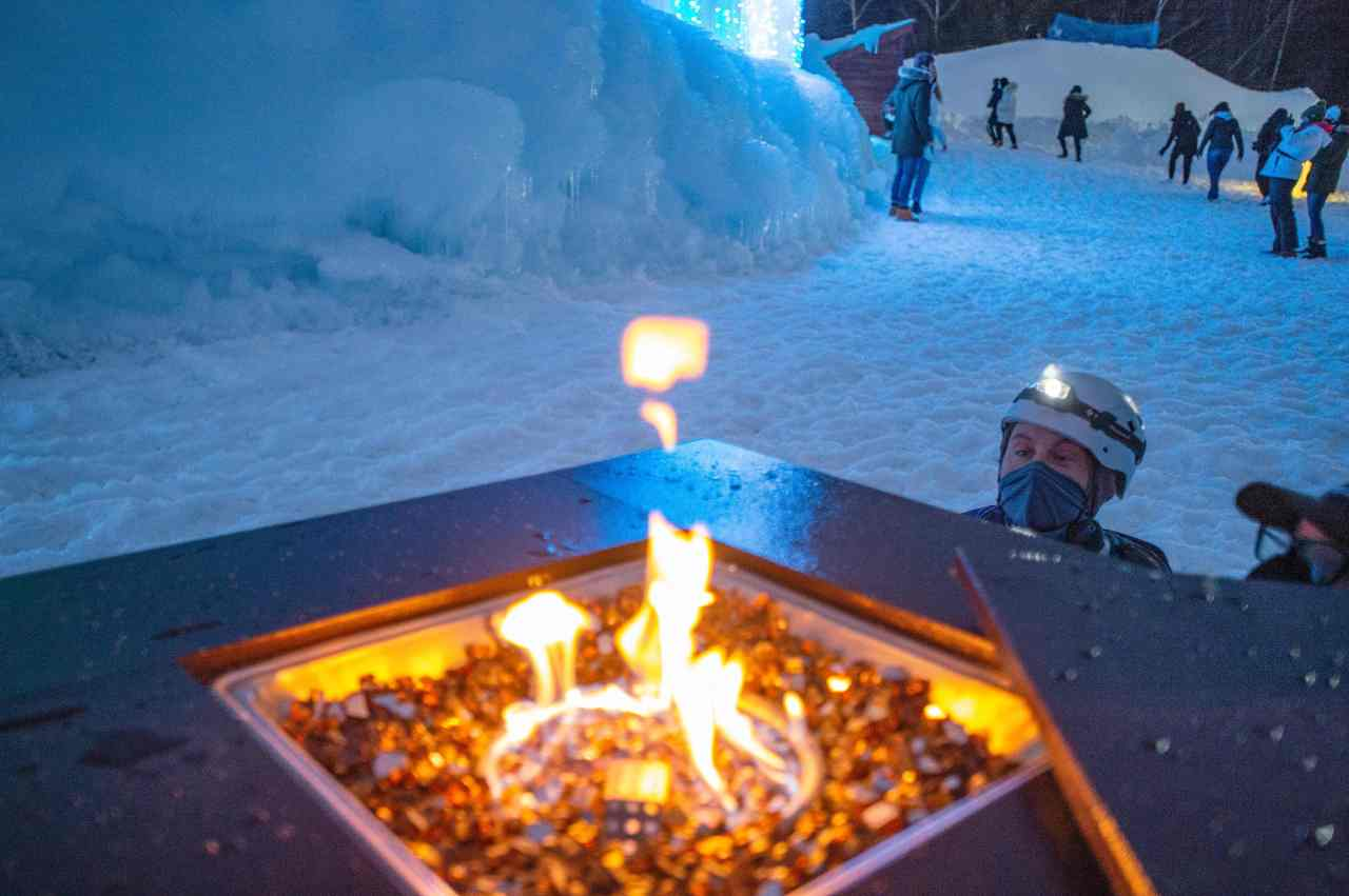 A worker lights a gas warmer at Ice Castles in North Woodstock, New Hampshire, on Thursday. (AFP-Yonhap)