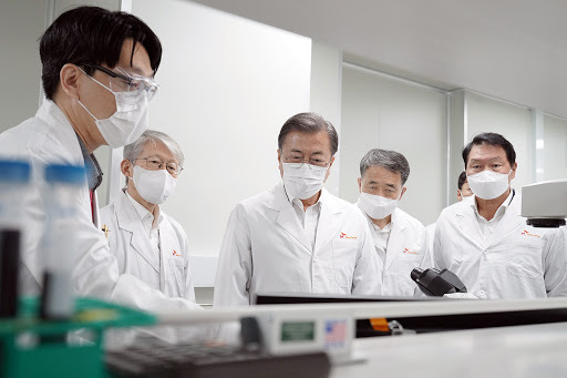 President Moon Jae-in (C) is briefed about vaccine research equipment during his visit to SK bioscience, a vaccine development company, in Seongnam, south of Seoul, on Oct. 15, 2020. (Yonhap)