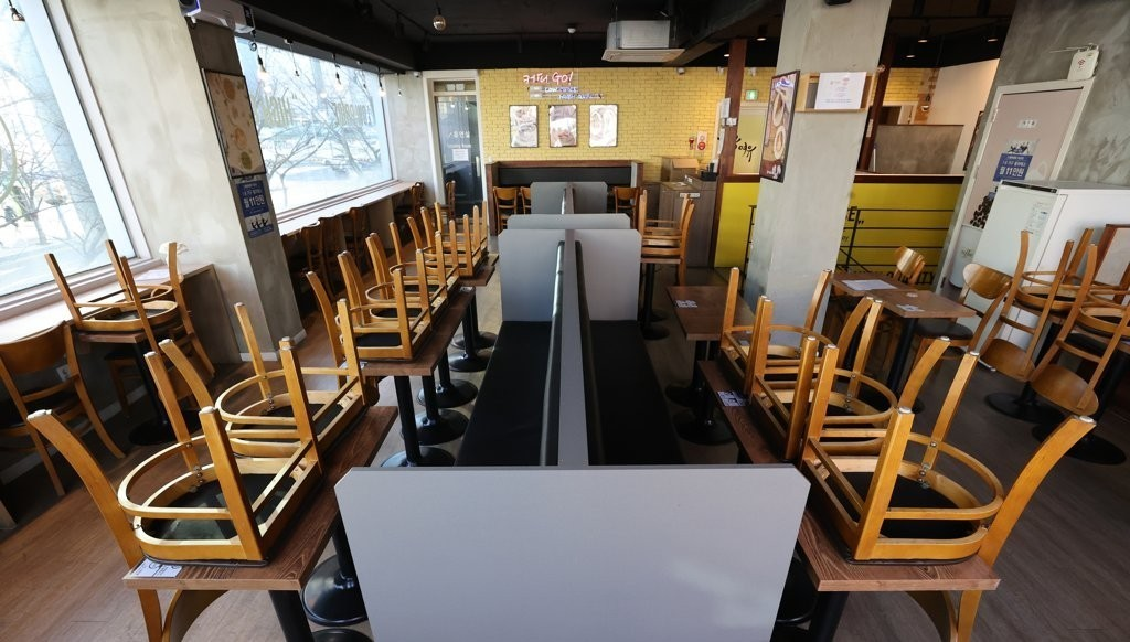 In this file photo, chairs are turned upside down on tables at a cafe in southern Seoul on Jan. 6, 2021, amid the government's COVID-19 restrictions on dining in at coffee shops. (Yonhap)