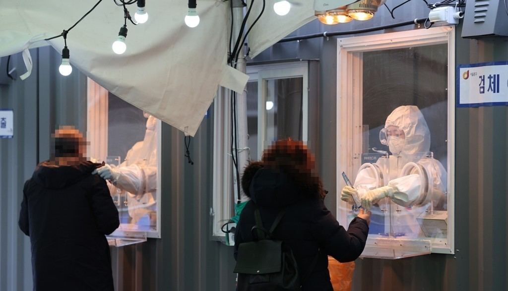 Medical workers collect specimens for coronavirus testing at a makeshift clinic in front of Seoul Station on Jan. 11, 2021. (Yonhap)
