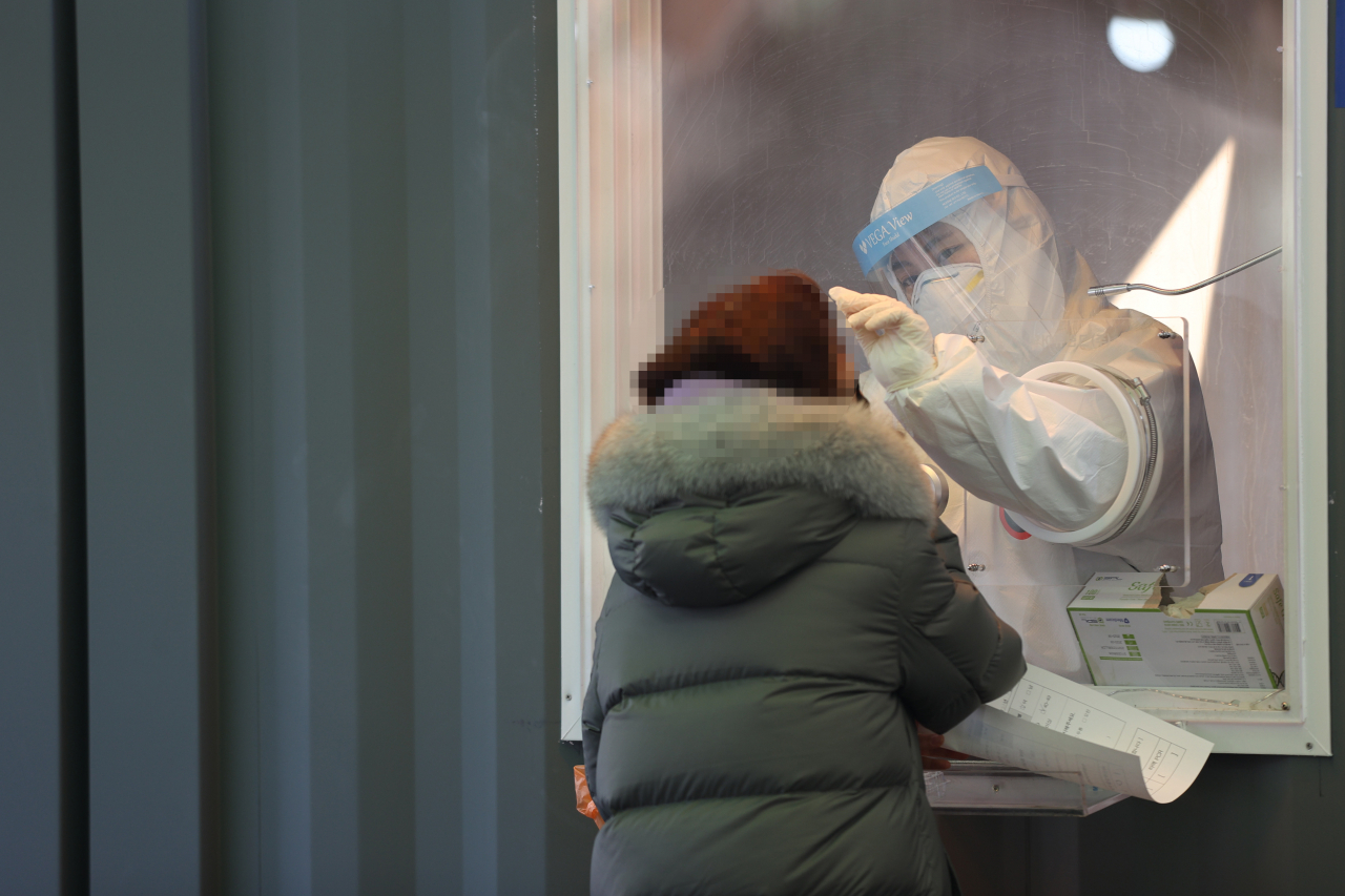 A medical worker collects a specimen from a woman at a temporary COVID-19 screening station set up in front of Seoul Station on Saturday. (Yonhap)