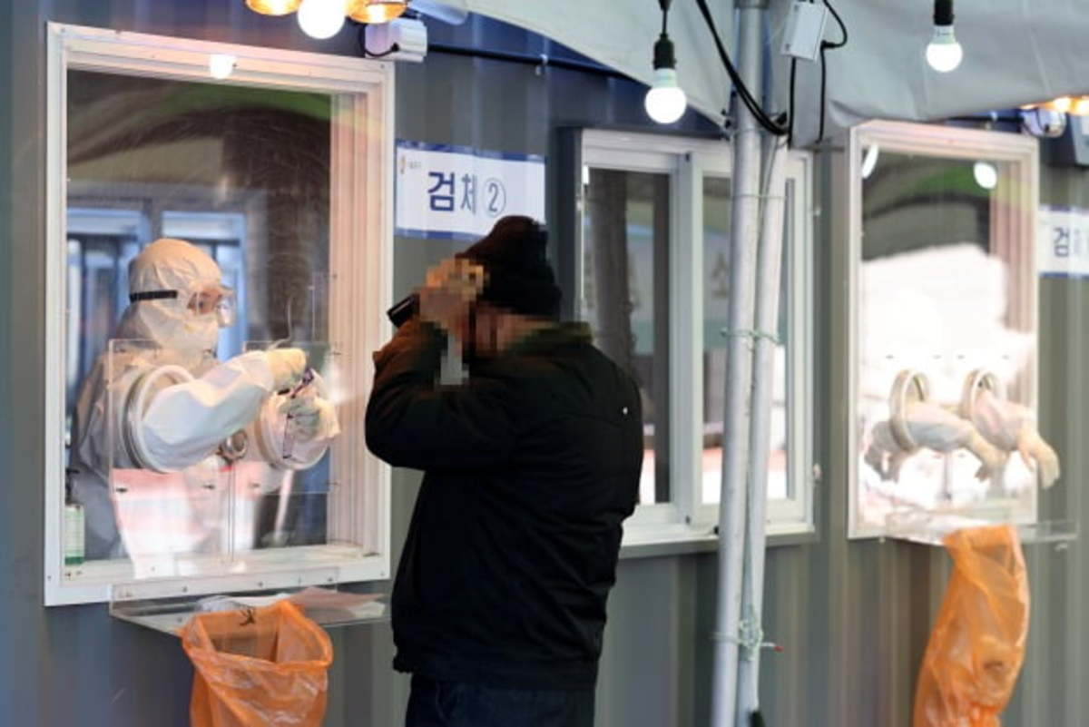 This photo taken on Sunday, shows a health worker collecting a sample from a citizen for the novel coronavirus test at a makeshift testing facility in Seoul. (Yonhap)