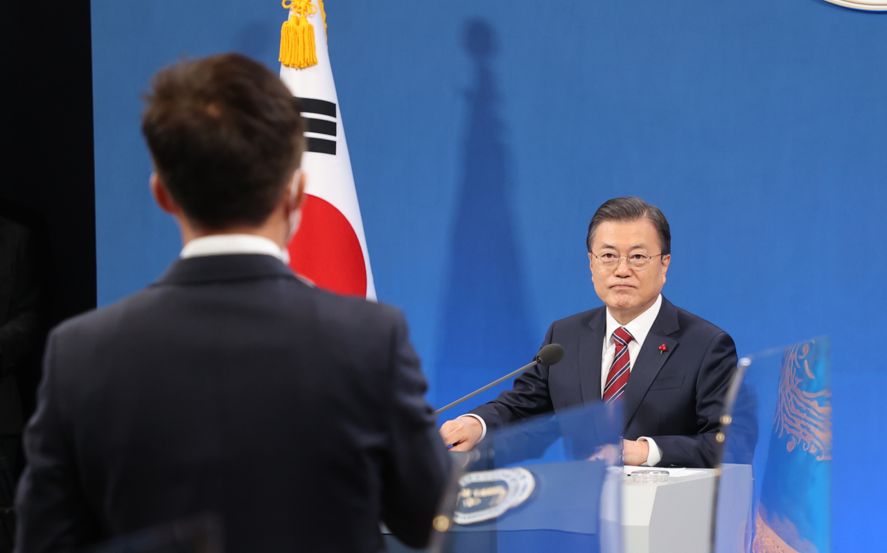 President Moon Jae-in (R) listens to a reporter's question during a New Year's press conference at the presidential office Cheong Wa Dae in Seoul on Monday. (Yonhap)