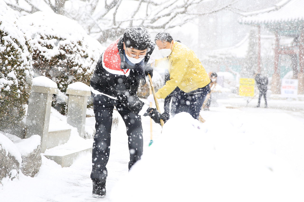 Civil servants remove snow from roads in Seosan in the central South Korean province of South Chungcheong on Monday, in this photo provided by Seosan City Hall. (Seosan City Hall)