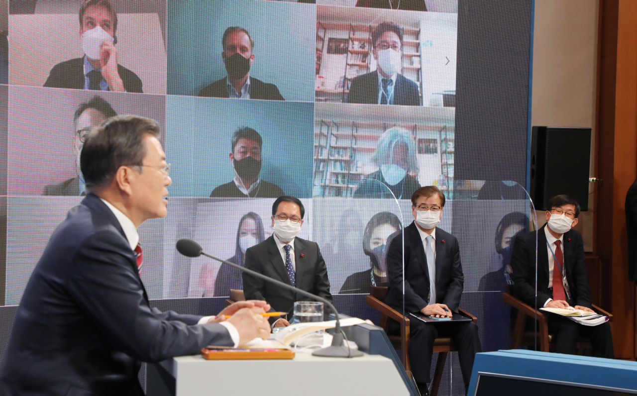 President Moon Jae-in speaks (L) during a New Year's press conference, also available via videoconference, at the presidential office Cheong Wa Dae in Seoul on Monday. (Yonhap)