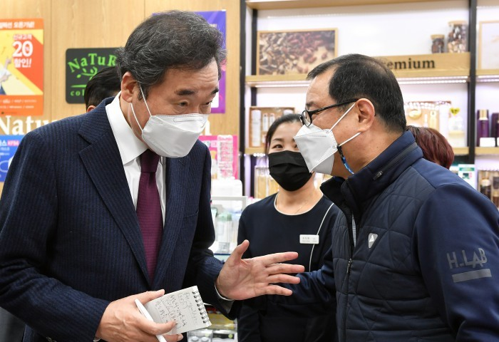 This photo provided by the National Assembly press corps shows Democratic Party Chairman Rep. Lee Nak-yon talking to a business owner in Seoul last Thursday, while inspecting business establishments hit by the new coronavirus pandemic. (National Assembly press corps)