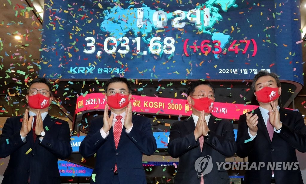 Officials at Korea Exchange celebrate during a ceremony to mark the benchmark Korea Composite Stock Price Index`s (KOSPI) breakthrough of the 3,000-point mark for the first time in its history on Jan. 7, 2021, when the index soared 63.47 points, or 2.14 percent, to close at 3,031.68 points.