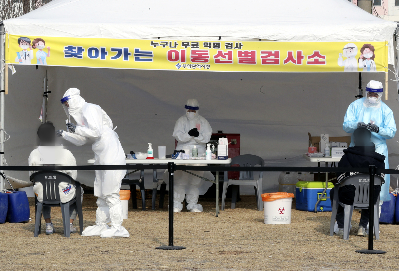 This photo taken on Monday, shows health workers clad in protective suits working at a makeshift virus testing clinic in Busan. (Yonhap)
