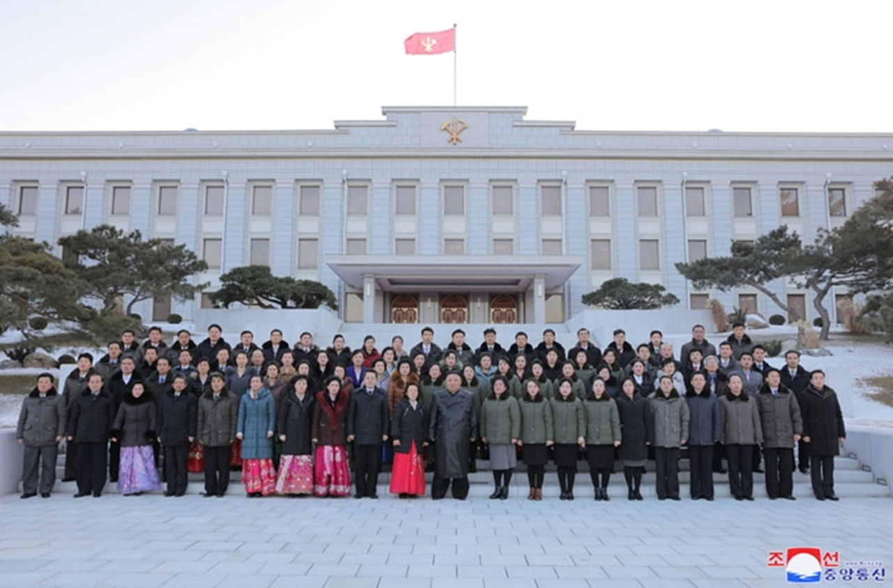 North Korean leader Kim Jong-un (C, 1st row) joins a group photo session with workers of the publishing and printing field who contributed to the recently concluded eighth congress of the North's ruling Workers' Party in Pyongyang on Monday, in this photo captured from the website of the North's official Korean Central News Agency the next day. (KCNA-Yonhap)