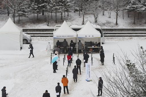 People wait in line to receive virus tests at a makeshift COVID-19 testing facility in Uijeongbu, north of Seoul, on Monday. (Yonhap)