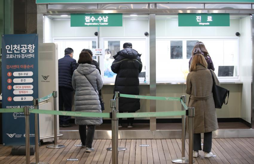 In this file photo, people apply for COVID-19 tests at a testing station set up for departing passengers at the second terminal of Incheon International Airport, west of Seoul, on Jan. 8, 2021. (Yonhap)