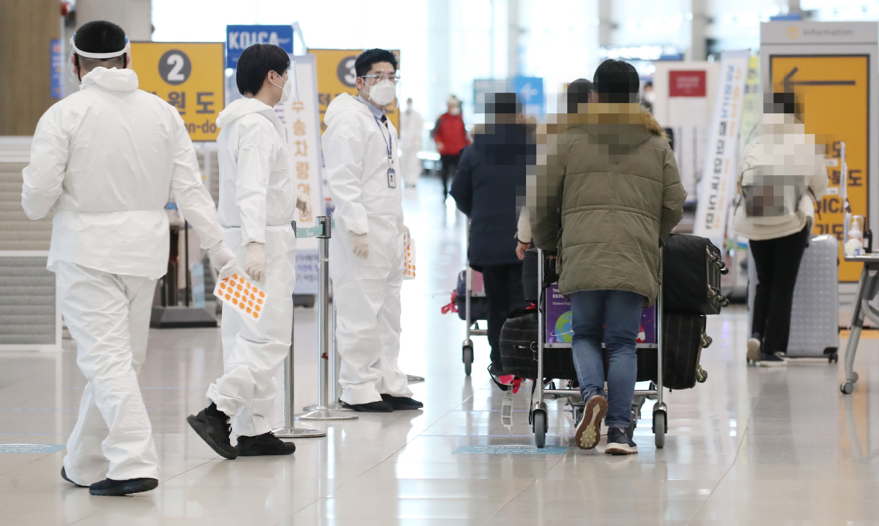 This photo taken on Tuesday, shows health workers clad in protective suits guiding arrivals at Incheon International Airport in Incheon. (Yonhap)