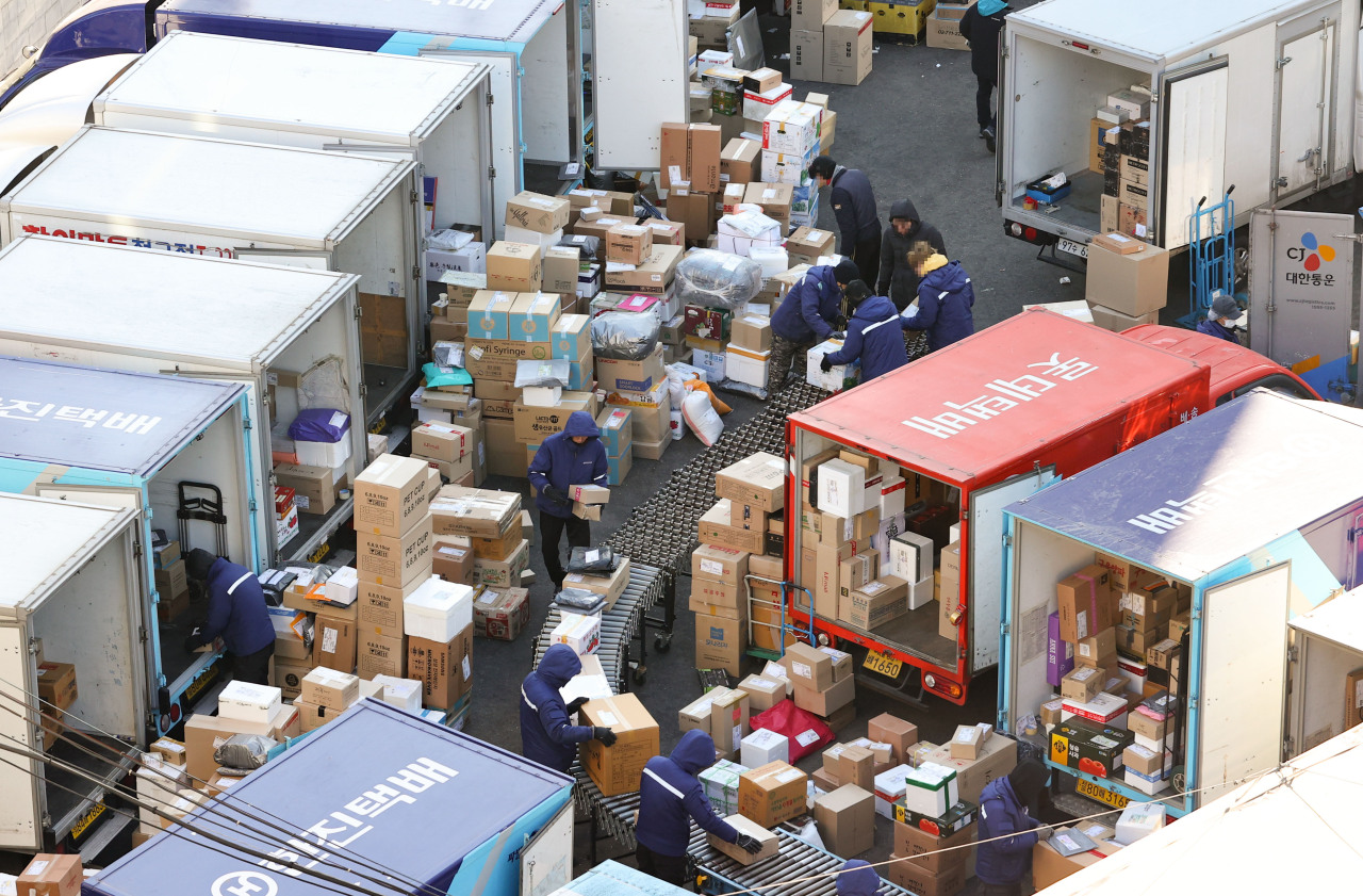 Parcel delivery workers move boxes Tuesday ahead of the Lunar New Year holiday next month. Unionized delivery workers are mulling to launch a full-scale walkout in their fight for better working condition and wages. (Yonhap)